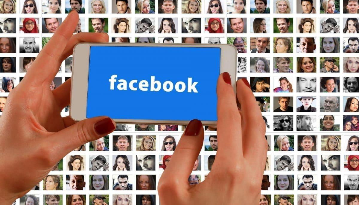 Facebook en una mano con fotos de fondo