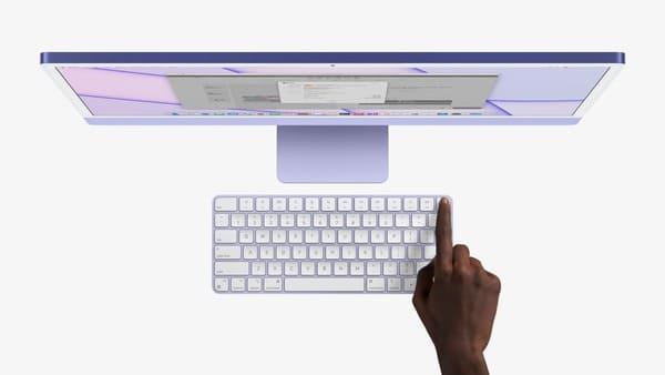apple-nuevo-imac-m1-2021-color-violeta-usando-touch-id-mano-persona-negra